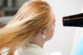 Woman s hair being blow dried blond of a young by dryer at parlor Stock Images