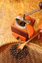 Woman`s hand cupping roasted coffee beans with wooden spoon from threshing basket to grinder for homemade coffee Royalty Free Stock Photo