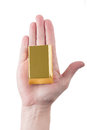Woman s hand with gold bar over white background Royalty Free Stock Image