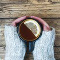Woman`s hand holding cup of tea with lemon on a cold day. Wooden table. Top view Royalty Free Stock Photo