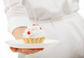 Woman's hand holding plate with a cake Royalty Free Stock Photo