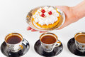 Woman`s hand holding small cake on beautiful set plate Royalty Free Stock Photo
