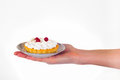 Woman`s hand holding small dessert cake on delicate set plate Royalty Free Stock Photo