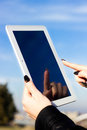 Woman s hand holding and touching digital tablet pc against the sky Royalty Free Stock Photography