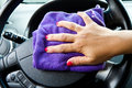 Woman s hand with microfiber cloth polishing wheel of a car Stock Image
