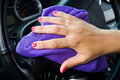 Woman s hand with microfiber cloth polishing wheel of a car Royalty Free Stock Image