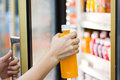 Woman`s hand open convenience store refrigerator shelves and pic Royalty Free Stock Photo