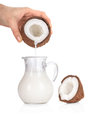 Woman's hand pouring coconut milk into a jar on white