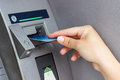 Woman s hand puts credit card into atm close up Royalty Free Stock Image
