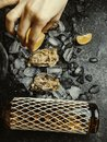 Woman's hand squeezes juice from lemon on oyster shell, dark stone background. Wine bottle and glass. Food aphrodisiac Royalty Free Stock Photo