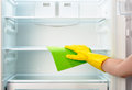 Woman's hand in yellow glove cleaning refrigerator with green rag Royalty Free Stock Photo