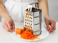 Woman s hands holdin a plate with grated carrot holding closeup shot Royalty Free Stock Photography