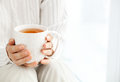 Woman`s hands is holding hot cup of coffee or tea in morning su Royalty Free Stock Photo