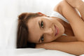 Woman s health smiling woman with beautiful face skin beauty closeup portrait of fresh soft having fun lying on white bed healthy Stock Photography