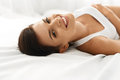 Woman s health smiling woman with beautiful face skin beauty closeup portrait of fresh soft having fun lying on white bed healthy Royalty Free Stock Image