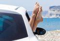 Woman s legs dangling out a car window near the sea Royalty Free Stock Photos