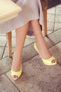 Woman s legs in light yellow open toe pumps woman sitting in a restaurant waiting for date Royalty Free Stock Photo