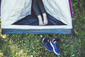 Woman's legs in open tent and her sport sneakers on grass. Royalty Free Stock Photo