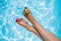 Woman`s legs over the swimming pool