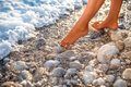 Woman's legs on the stone beach with water Royalty Free Stock Photo