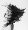 Woman s long hair flying young in motion blur effect monochrome image Stock Photo