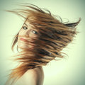 Woman s long hair flying young in motion blur effect toned image Royalty Free Stock Image