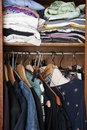 Woman s wardrobe with clothes hanging narrow and messy female Stock Photo