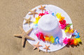 Woman s white hat on the sandy beach with starfishes and decoration Stock Photos