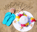 Woman s white hat on the sandy beach with starfishes decoration flip flops and sign vacation Royalty Free Stock Photo