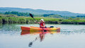 Woman with safety vest kayaking alone on a calm river young and wearing Royalty Free Stock Photography