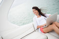 Woman sailing on a yacht with a laptop and using computer Royalty Free Stock Photos