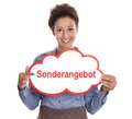 Woman at sales isolated with a red advertising board or sign special offer pretty in blue shirt holding german speech bubble Stock Photography