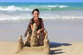 Woman and a sand castle pretty vacationing behind at the beach sandy beach clear blue ocean waves Stock Images
