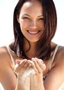 Woman with sand falling through fingers close up portrait of a beautiful smiling Stock Images