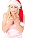Woman in santa claus hat blows on open hands Royalty Free Stock Photo