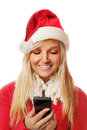 Woman with santa hat beautiful young in costume wearing a christmas and looking at her smartphone white studio shot Royalty Free Stock Photos
