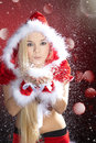Woman with santa hat blows the snow Royalty Free Stock Photo