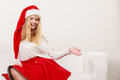 Woman in santa hat with empty hand for copy space happy smiling cute helper open palm pretty blonde girl studio on gray Stock Photos