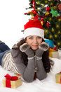 Woman in santa hat and fur mittens lying under christmas tree cute Stock Photography