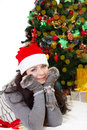 Woman in santa hat and fur mittens lying under christmas tree smiling Stock Photos