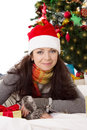Woman in santa hat and fur mittens lying under christmas tree smiling Royalty Free Stock Images