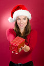 Woman with santa hat giving a christmas gift box Stock Photography