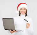 Woman in santa hat with laptop and credit card christmas x mas online shopping concept helper computer Royalty Free Stock Images