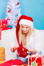 Woman in Santa hat packing christmas gifts