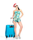 Woman in santa hat  standing with travel suitcase Royalty Free Stock Image
