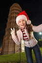 Woman in Santa hat taking selfie and showing victory in Pisa Royalty Free Stock Photo