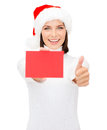 Woman in santa helper hat with blank red card christmas x mas people advertisement sale concept happy showing thumbs up Royalty Free Stock Photos