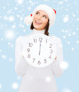 Woman in santa helper hat with clock showing 12 Royalty Free Stock Photography