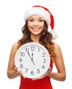 Woman in santa helper hat with clock showing christmas x mas winter happiness concept smiling Royalty Free Stock Images