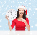Woman in santa helper hat with clock showing christmas x mas winter happiness concept smiling Stock Photos